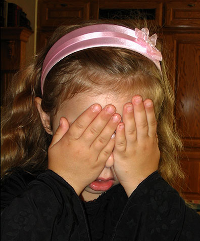 Sorrowful girl covering her eyes with her hands
