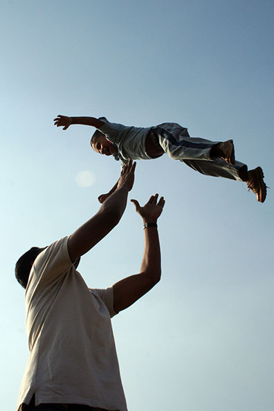 Parent lifting child high into the air