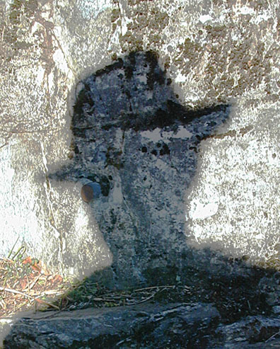Shadow of man with hat cast onto a crusty wall