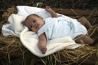 Baby in swaddling clothes, lying in a manger of hay