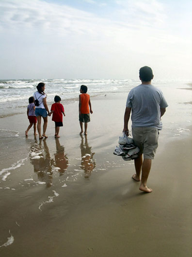 A family walking along an ocean beach